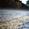 A close up view of rain drops hitting a road.